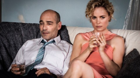 Ray-(Jean-Marc-Barr)-_-Iris-(Radha-Mitchell)-on-the-couch-Photo—Mark-Rogers